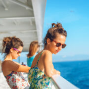 Two young women girl friends sisters standing by the fence on deck of the ferry boat or ship sailing to the island tourist destination on summer vacation looking to the sea in sunny day